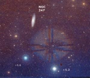 Una fotografia della regione centrata sulla galassia NGC 247; il campo inquadrato misura 2,4° nel lato lungo. Le due luminose stelle in basso sono la SAO 166585 (a sinistra) e la SAO 166528. L'alone luminoso al centro è un riflesso proveniente da Deneb Kaitos, situata quasi 3° più a nord.